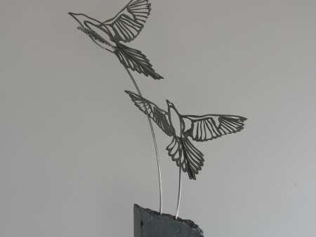 Stainless steel plate figure of two birds on freestone pedestal.