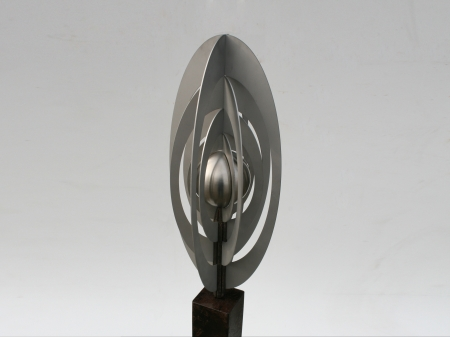 Stainless steel display of a metal ball surrounded by blades of metal sheets, placed on a freestone pedestal. Afmeting: 148 x 20 x 20 cm. Series of 5, of which 2 sold.
