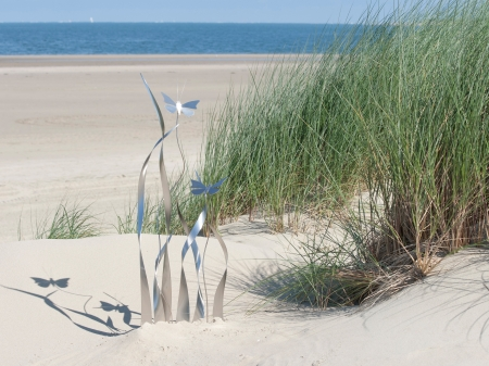 Stainless steel display of whirling butterflies in high marram grass. 