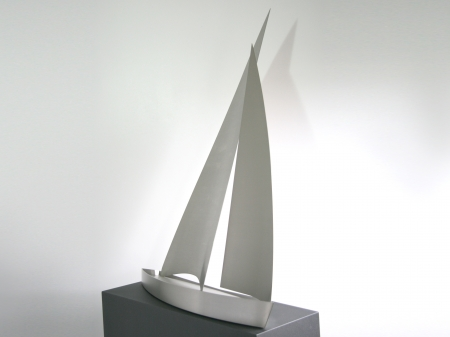 A threedimensional display of a stainless steel sailing boat, placed on metallic powder coated pedestal. Measurements: Object 102 x 90 x 50 cm, pedestal 118 x 90 x 32 cm. 