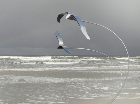 Two stainless steel seagulls placed on unifying curved rods. With a little bit of airflow, the rods will make the seagulls move in the wind. 